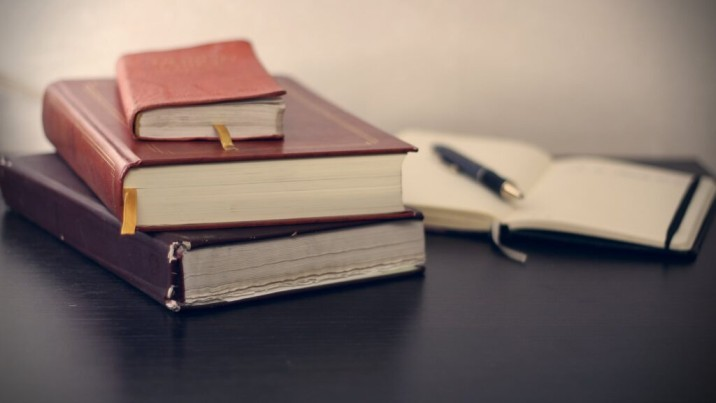 stack of books with pen and pad in background