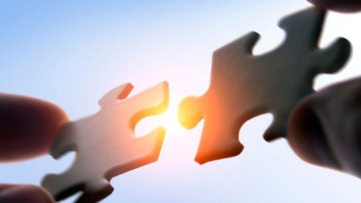 Two businessman connecting puzzle pieces togheter