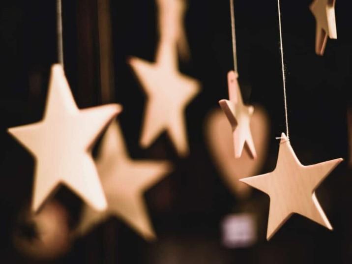woodern stars hanging by string black background